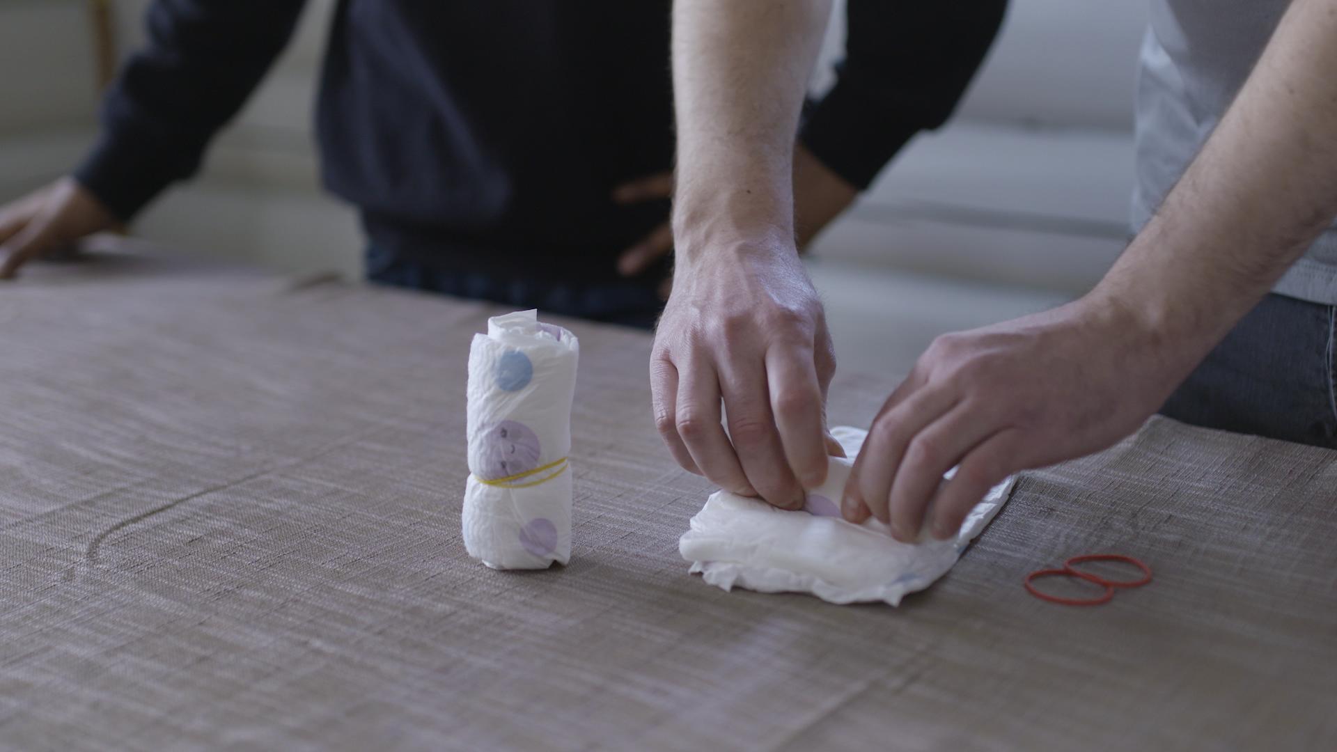 Rull sammen en bleie og sett strikk rundt. Gjør dette med tre bleier.
