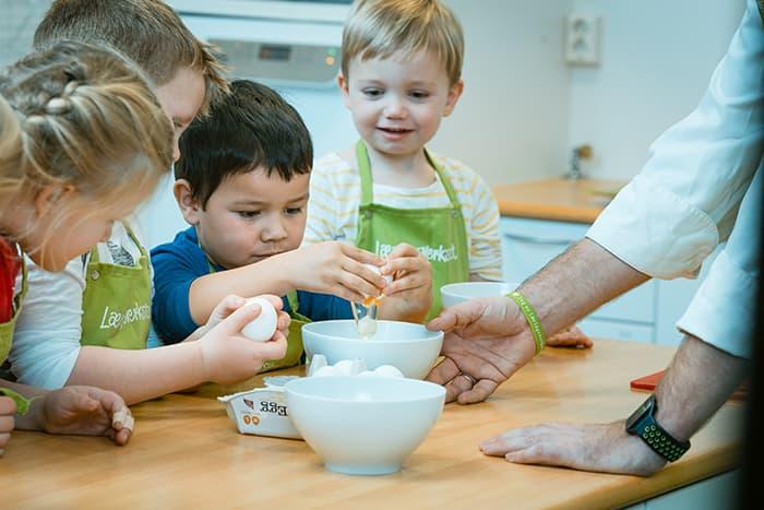 Daniel (4) får knekke eggene som skal brukes til å panere laksefiletene. Foto: Nina Holtan