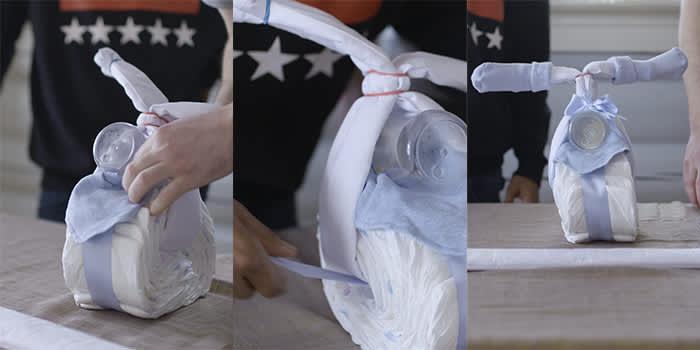 Smett siklesmekken mellom tåteflaska og hjulet. Trekk silkebåndet gjennom hjulet og over flaska.