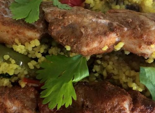 Couscous and Mediterranean vegetables roasted with garlic & whole spices & topped with marinated chicken skewers