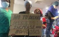 One of the protesters holding a placard during demonstrations over wages at the Charlotte Maxeke Academic Hospital in Johannesburg on 31 May 2018. Picture: Christa Eybers/EWN