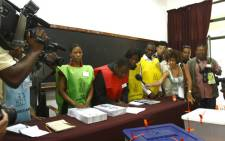 A municipal employee, flanked by other workers, signs documents during the fourth Mozambican general elections in Maputo on 28 October 2009. Picture: AFP