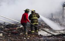 Fire fighters put out smoldering embers amid the debris left by a huge blast that occured in a fireworks market in Mexico City, on 20 December, 2016 killing at least 26 people and injuring scores. Picture: AFP.