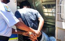 The suspect accused of raping a six-week-old baby in Galeshewe, Northern Cape is put into a police van. Picture: Supplied.
