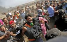 Palestinians carry a demonstrator injured during clashes with Israeli forces near the border between the Gaza strip and Israel east of Gaza City on 14 May 2018, as Palestinians protest over the inauguration of the US embassy following its controversial move to Jerusalem. Picture: AFP
