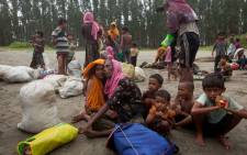 This undated photo shows newly arrived Rohingya refugees sit at Shamlapur beach in Cox's Bazar district, Bangladesh, after travelling for five hours in a boat across the open waters of the Bay of Bengal. Picture: Unicef