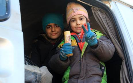 Syrian children, who were evacuated from the last rebel-held pockets of Syria's northen city of Aleppo, flash the sign of victory upon their arrival on 19 December 2016. Picture: AFP.