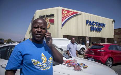 A man drops meat hampers - packets containing multiple products that cost roughly R200 - with security officials outside the Enterprise factory in Germiston. Picture: Thomas Holder/EWN