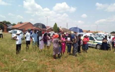 Shocked Dobsonville residents stand near to where the bodies of two teenage girls were discovered on 19 February. Picture: Masego Rahlaga/EWN.