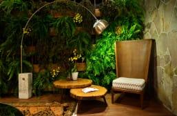 Cadeira alta com luninária e plantas ao fundo.