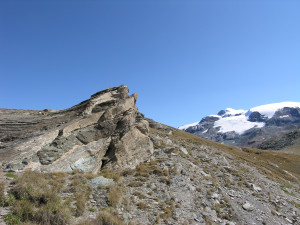 Alternanze di metabasiti (antiche lave di fondo oceanico) e calcescisti (antichi sedimenti oceanici) sovrapposti e ripiegati. Sullo sfondo il Monte Rosa.