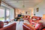 Sitting room with log burner and panoramic views of Snowdonia and Cardigan Bay