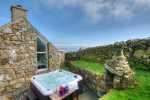 Slate terrace with outdoor fireplace, hot-tub and barbecue