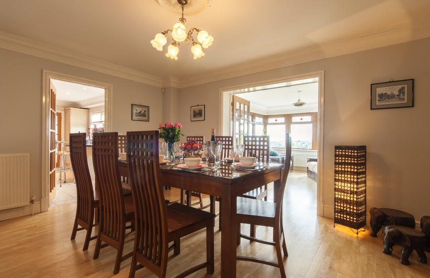 Indonesian teak glass topped dining table leading to the conservatory