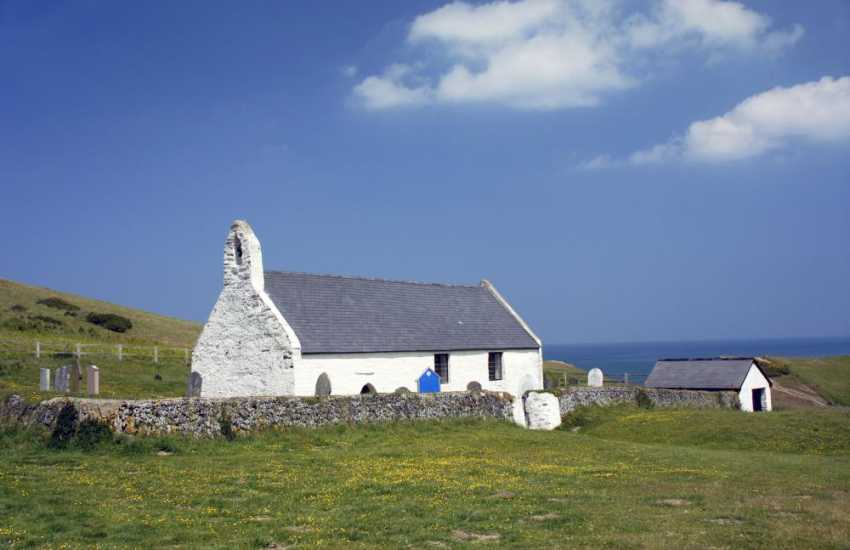 The tiny 15th century Church of the Holy Cross sits high on the cliffs overlooking the beach at Mwnt