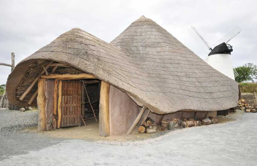 Reproductions of Iron Age Huts alongside Llynnon Mill are a popular visitor attraction