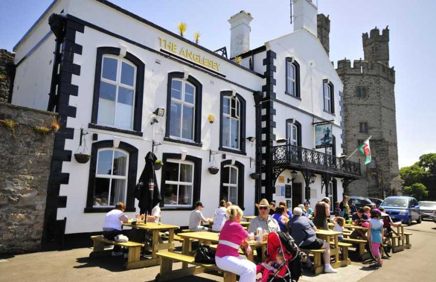 Caernarfon castle and its walled streets lined with shops, cafe, restaurants and pubs