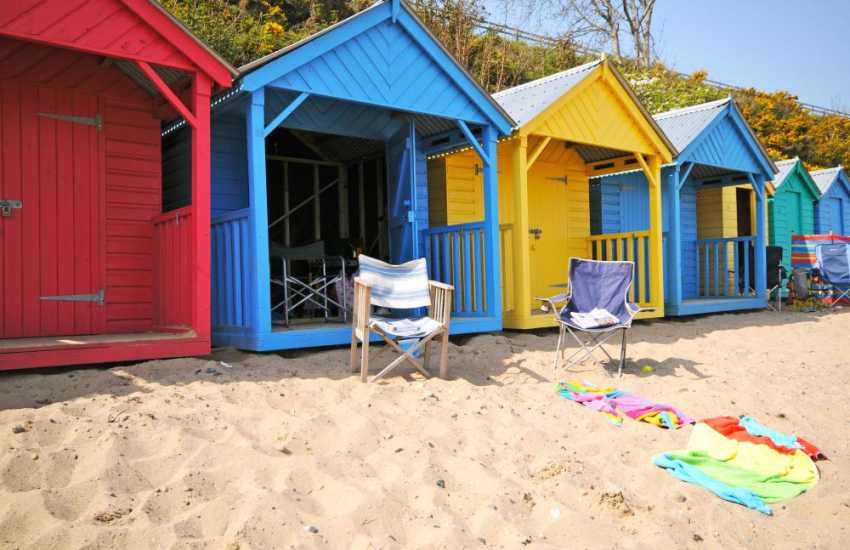 Chill out in one of the colourful huts at Llanbedrog beach