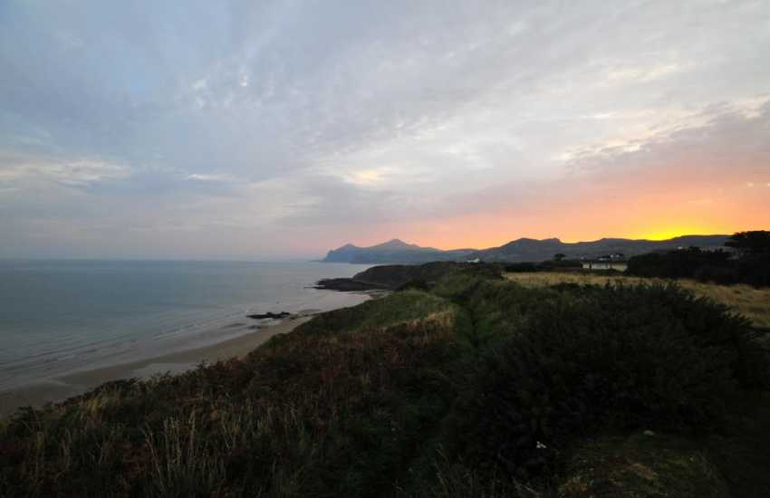 The sun rising behind the mountain at Nefyn