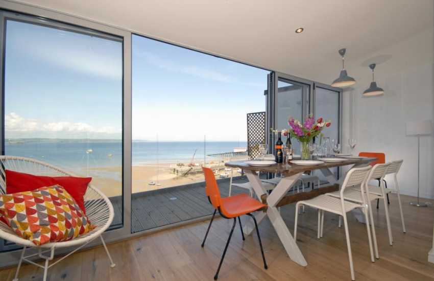 Tenby holiday home - dining area with bi-fold doors to the decked terrace