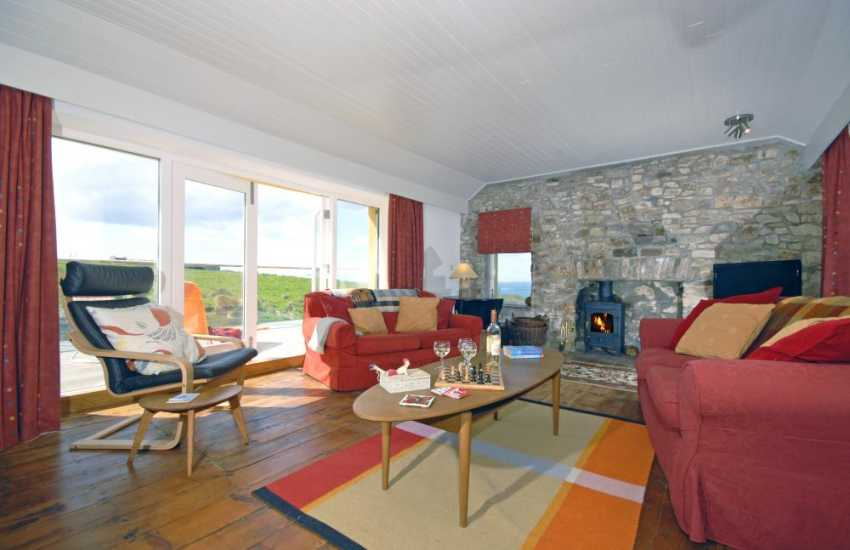 Pembrokeshire holiday home - lounge with patio doors to deck, sea views and wood-burning stove