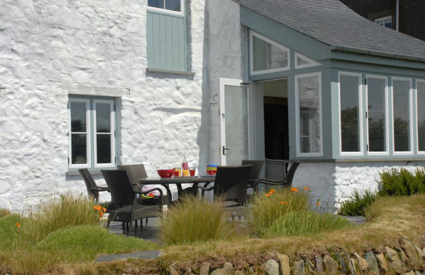 St Davids self-catering holiday barn - patio seating area off conservatory