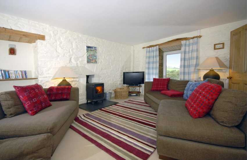 Cardigan Bay holiday house - family sitting/games room with wood burning stove, countryside and garden views