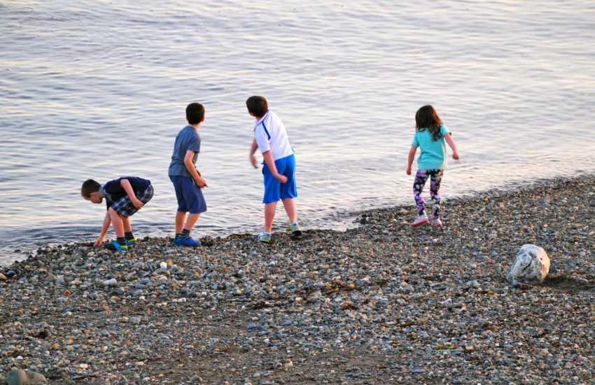 Children playing on Criccieth Beach as the sun goes down
