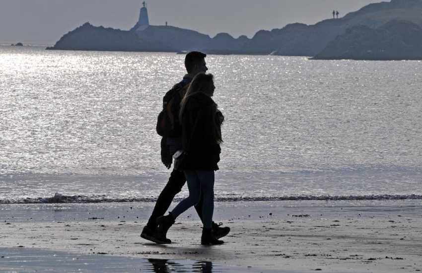 Walkers on Newborough beach as the sun goes down