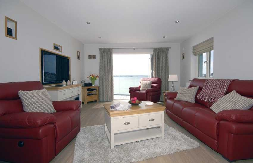 Haven Waterway holiday apartment - open plan lounge with bi-folding doors to balcony and river views