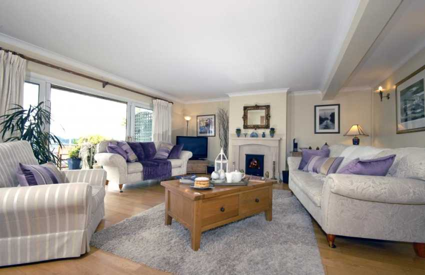 South Pembrokeshire holiday home on the Milford Haven Waterway - lounge with patio doors to the deck and gas fire