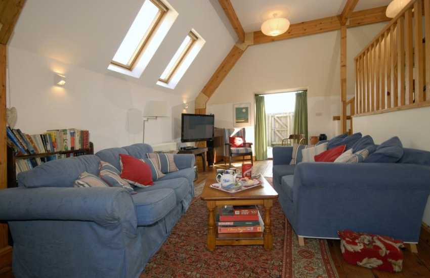 Dunraven Bay holiday cottage - mezzanine sitting room with digital t.v and french doors to the gardens