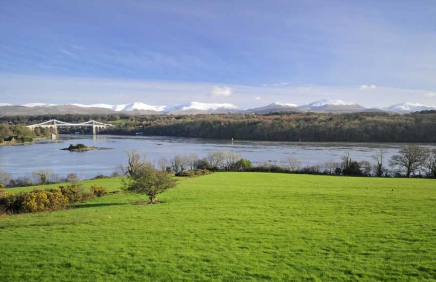 The Menai Suspension Bridge with snow capped Snowdonia beyond. Take a pleasure flight along this fabulous coastline from the airport near Dinas Dinlle