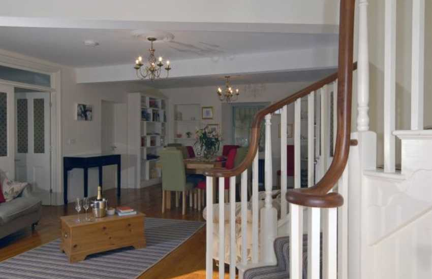 The elegant staircase leads from the sitting/dining room up to the first floor
