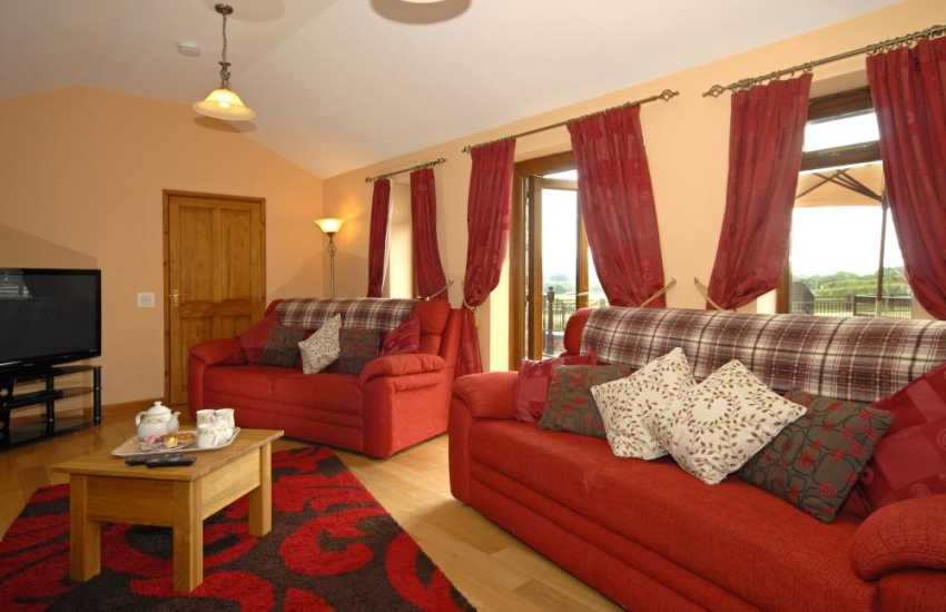 Gower holiday cottage - cosy sitting room with French doors to patio