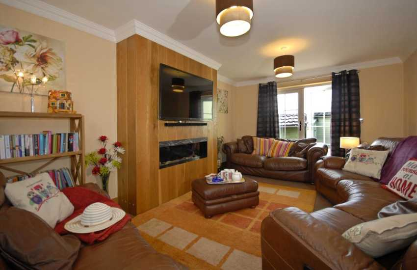 Solva Pembrokeshire modern holiday home - living room with Letter Box gas fireplace and patio doors to garden