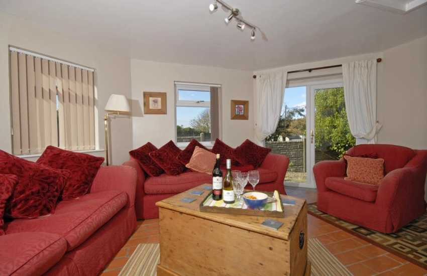 Abercastle family holiday home, sun room with t.v. and patio doors to the garden
