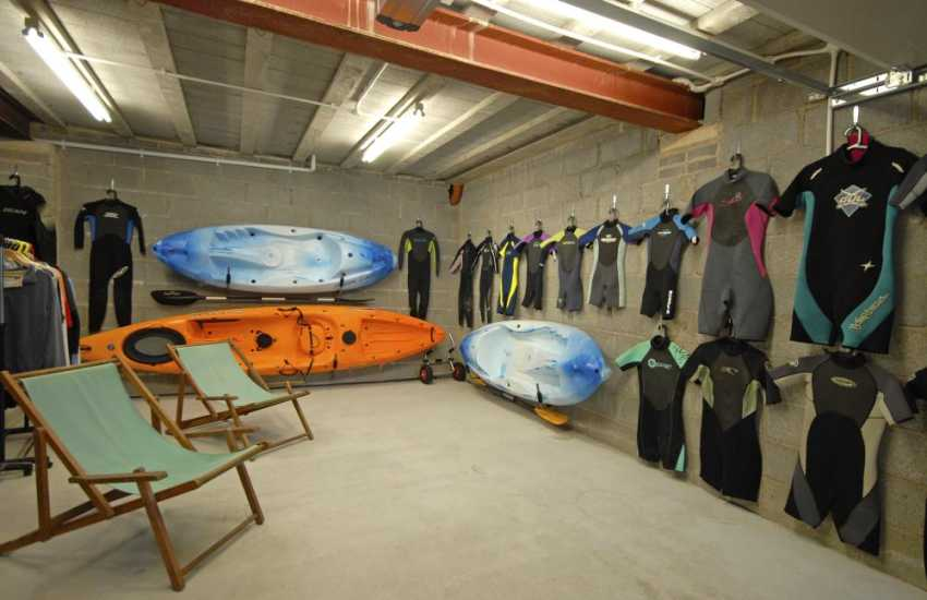 Garage with wetsuits kayaks and deck chairs