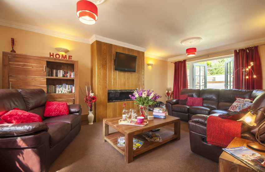 Solva Pembrokeshire modern holiday home - living room with gas effect fireplace and patio doors to garden