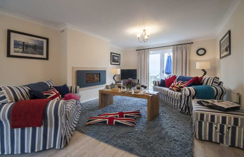 Llansteffan Beach modern holiday home with spacious sitting room with gas fireplace and patio doors to gardens