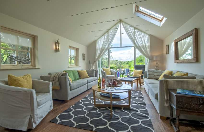 Manorbier coastal holiday cottage - family room with a glass gable end and double doors opening to the garden