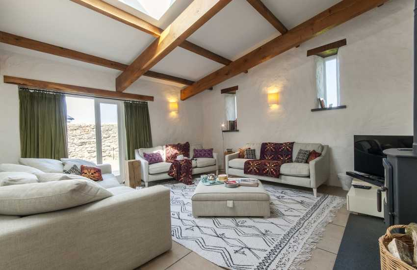 Pembrokeshire barn conversion - sitting room with comfy seating and patio doors to courtyard