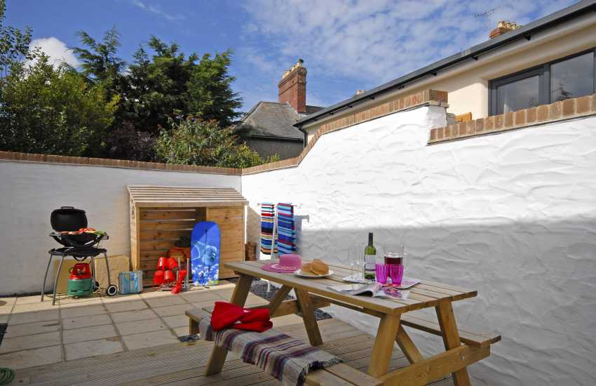 Rear sheltered patio with BBQ and picnic bench