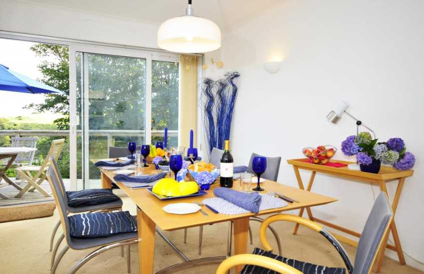 Dining room with patio doors onto the sun deck in holiday cottage - Anglesey