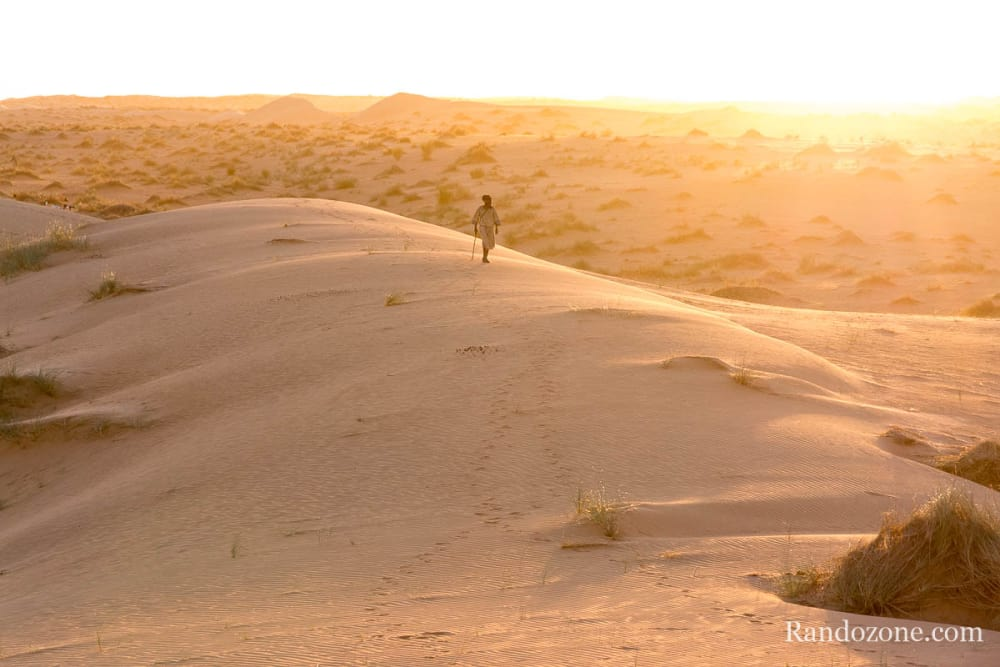Un berger marche sur les dunes dans le soleil couchant