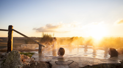 mornington peninsula hotel group of people with in a hot springs pool at sunset looking off in the distance