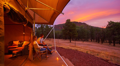 couple sitting on a deck outside glamping tent at sunset