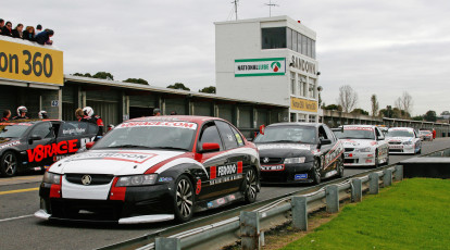 cars lined up on a race track waiting to start a race