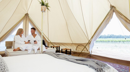 woman and man in bathrobes relaxing on a sofa inside a glamping tent in a vineyard