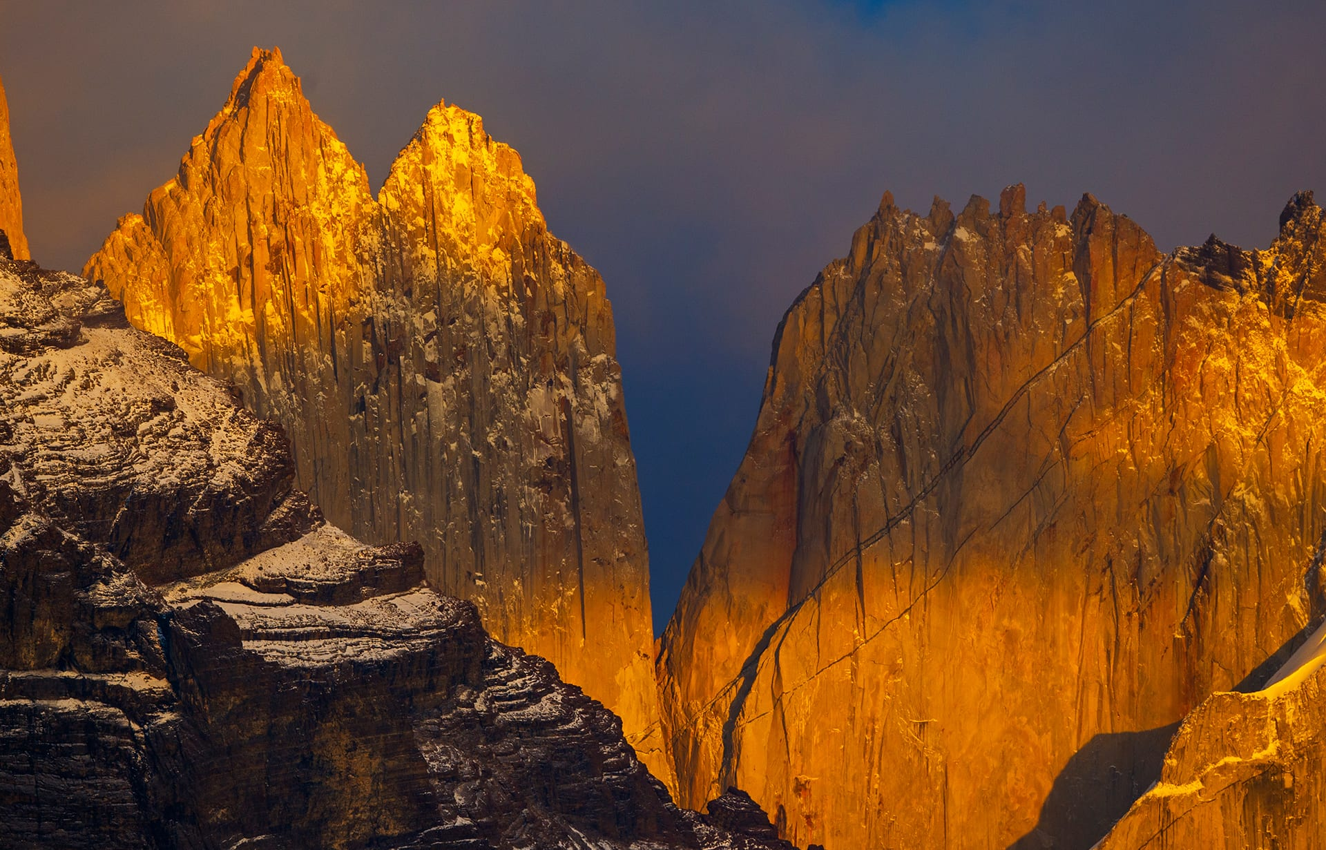 """The three granite peaks are the Torres del Paine or """"towers of blue"""". They are surrounded by spectacular glaciers and glacial lakes, rivers and waterfalls, wildlife and wilderness. At sunrise, I caught them looking more like slabs of gold, dusted with bits of snow, than blue granite."""